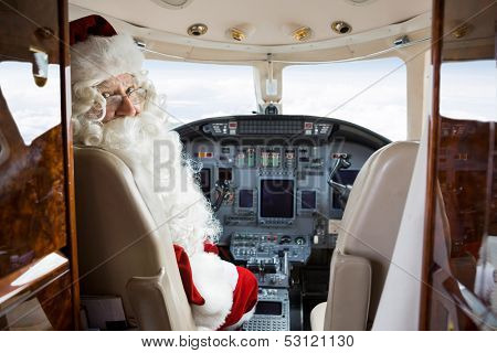 Portrait of Santa sitting in cockpit of private jet