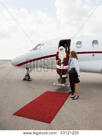 Santa disembarking private jet while pilot and airhostess standing by at airport terminal