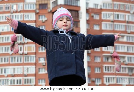 Little Girl With Divorced Hands Against Background Building