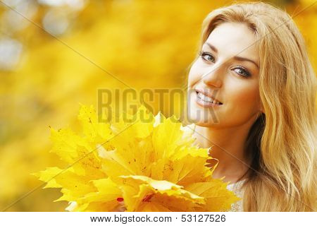 Portrait of a beautiful smiling woman in the autumn park