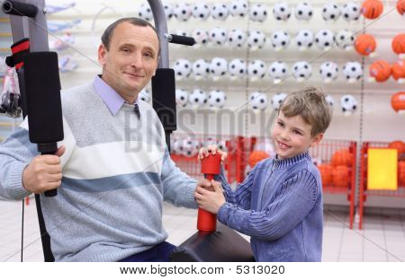 Elderly Man In Shop On  Sports Exerciser And Boy With Barbell In