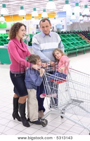 Elderly Man And  Young Woman With Children In Shop With Empty Sh