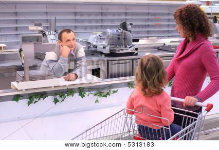Young Woman With Child And Bored Seller In Shop With Empty Shelv