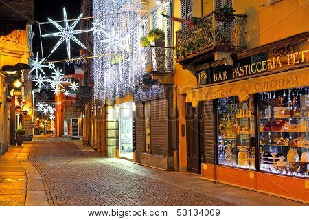 ALBA - DECEMBER 03: Popular tourist street in old historic center with shops, bars and restaurants illuminated and decorated for Christmas and New Year holidays in Alba, Italy on December 03, 2010.