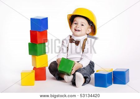 little engineer with helmet plays with cubes