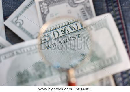 100 Usd Banknote Is Under The Examination Of A Magnifying Glass