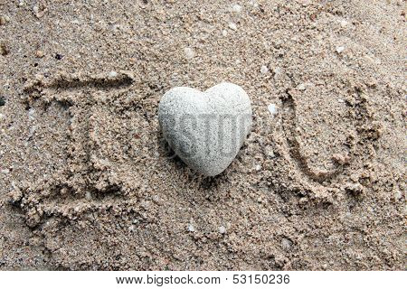 Grey stone in shape of heart, on sand background