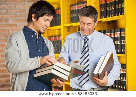 Happy male student holding books while discussing with librarian in college library