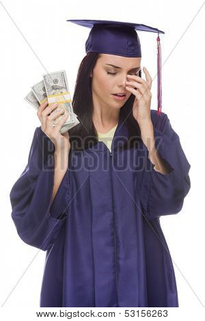 Stressed Female Graduate in Cap and Gown Holding Stacks of Hundred Dollar Bills Isolated on a White Background.