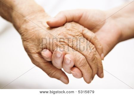 Adult Helping Senior In Hospital