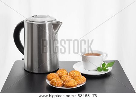 Electric Kettle, Cup Of Tea And Cookies On A Table