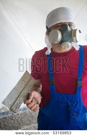 Working in a respirator with a spatula in hand