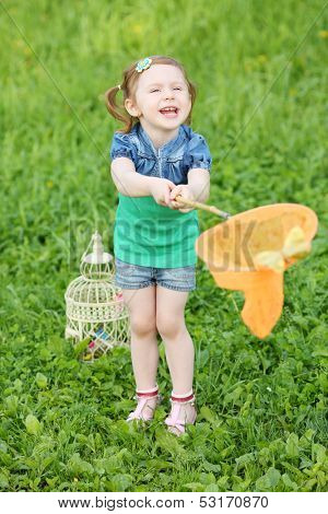 Little laughing girl holds orange butterfly net on green meadow.