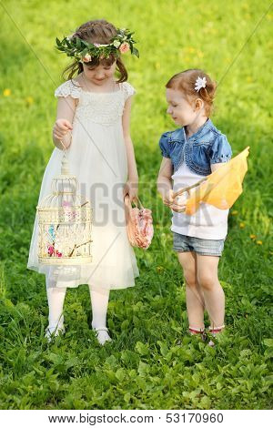 Two little girls play with net and butterflies in cage on green meadow.