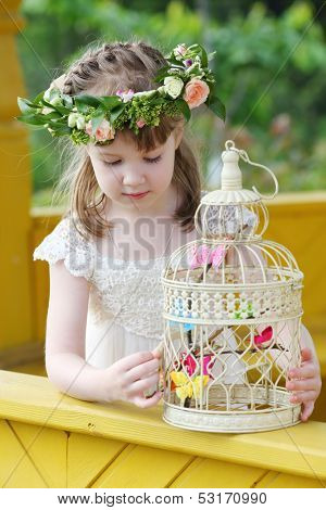 Little pretty girl in white dress and wreath plays with cage with butterflies.