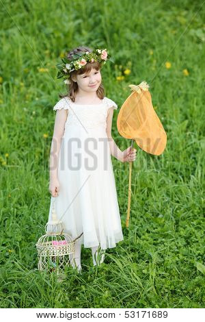Little girl in white stands with butterfly net and coop on green meadow.