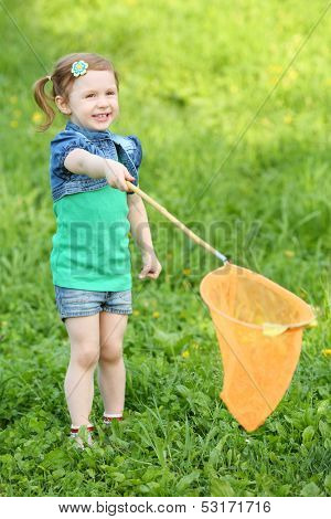 Little smiling girl holds orange butterfly net on green meadow.