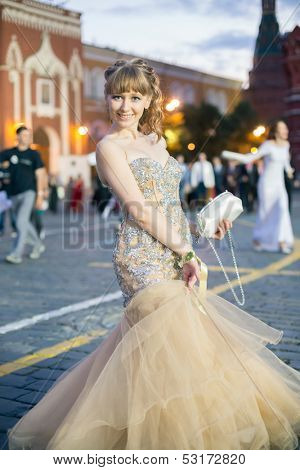 A beautiful young girl in elegant dress on the Red Square in Moscow