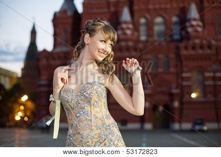 A smiling girl in a beautiful dress on Red Square near the Historical Museum