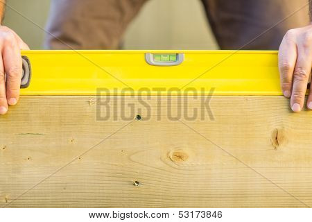 Closeup of manual worker holding spirit level on wood outdoors