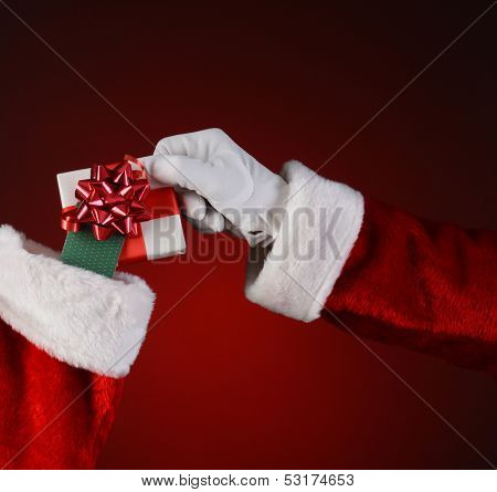 Closeup of Santa Claus placing a small wrapped present into a holiday stocking.  Square format on a light to dark red spot background.