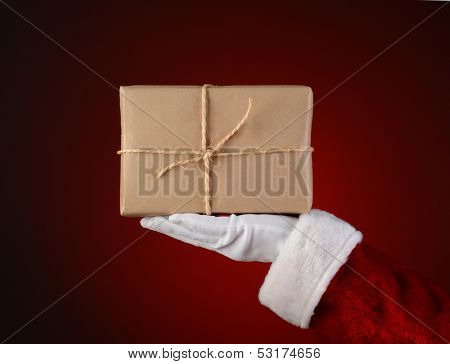 Closeup of Santa Claus holding a parcel in the palm of his outstretched hand. Hand and arm only over a light to dark red spot background.
