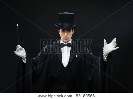 performance, circus, show concept - magician in top hat with magic wand showing trick