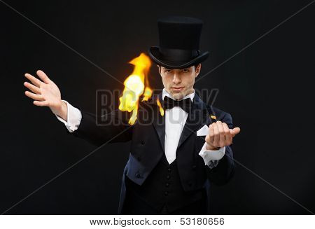 magic, performance, circus, show concept - magician in top hat showing trick with fire