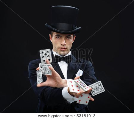 magic, performance, circus, gambling, casino, poker, show concept - magician in top hat showing trick with playing cards