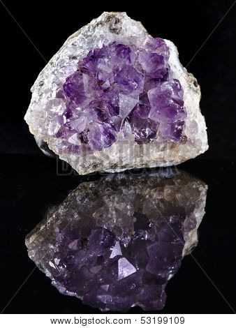 Natural cluster of Amethyst, violet variety of quartz close up macro with reflection on black surface background