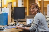 picture of librarian  - Smiling female librarian holding a book standing behind the desk looking at camera - JPG