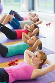 picture of crunch  - Side view of sporty fitness class doing sit ups on exercise mats - JPG