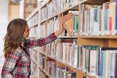 Pretty student placing book in shelf in library