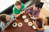 image of canteen  - Four smiling students having a cup of coffee chatting in college canteen - JPG