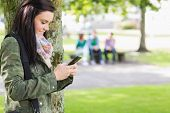 stock photo of down jacket  - Side view of a college girl text messaging with blurred students sitting in the park - JPG
