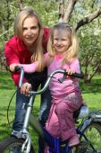 Mother With  Daughter On Bicycle In Spring Garden