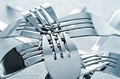 closeup of a pile of forks on a set table with a textured tablecloth