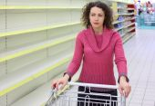 pic of stagnation  - young woman with cart in shop with empty shelves - JPG