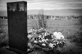 picture of tribute  - black tomb with floral tributes at cemetery - JPG