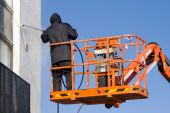 stock photo of cherry-picker  - Woker In Black Unifom Wash A White Building Wall at The Cherry Piker Platform - JPG