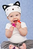 stock photo of skunks  - Happy baby playing with flowers in the hat skunk sitting on a blue background - JPG