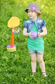 picture of bolero  - Little pretty girl holds ball and stands near mini basketball hoop at green meadow - JPG