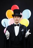 performance, circus, show, birthday party concept - magician in top hat with magic wand and colorful