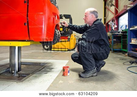 Mechanic repainting a forklift on a bridge in a workshop