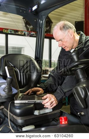 A man working on forklift, filling in some date of the forklift.