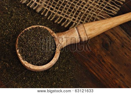 Olive wood scoop with dried green tea leaves on rustic dark wood background with burlap.  Low key still life with directional natural lighting for effect.