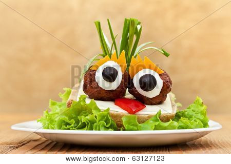 Funny meatball sandwich with vegetables, cheese and lettuce