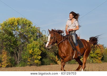 Beautiful girl  riding a horse on autumn field
