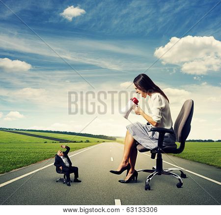 discontented big woman screaming at small frightened senior man on the road