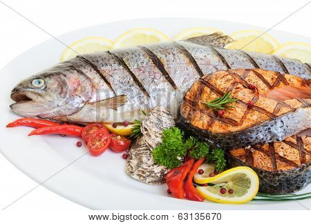 Close up Grilled trout and salmon steaks with vegetables and oysters